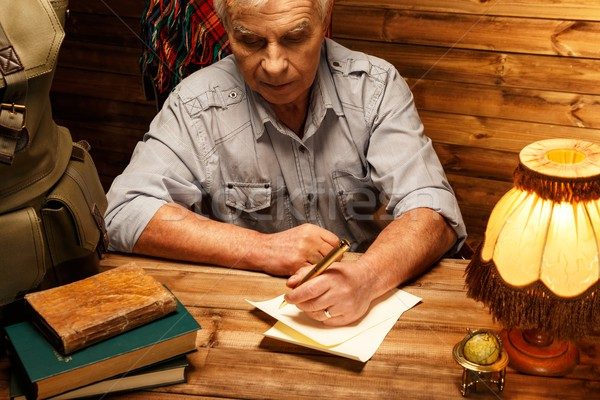 Senior writing letter with quill pen in homely wooden interior  Stock photo © Nejron