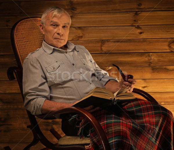 Senior man with smoking pipe sitting on rocking chair in homely wooden interior Stock photo © Nejron