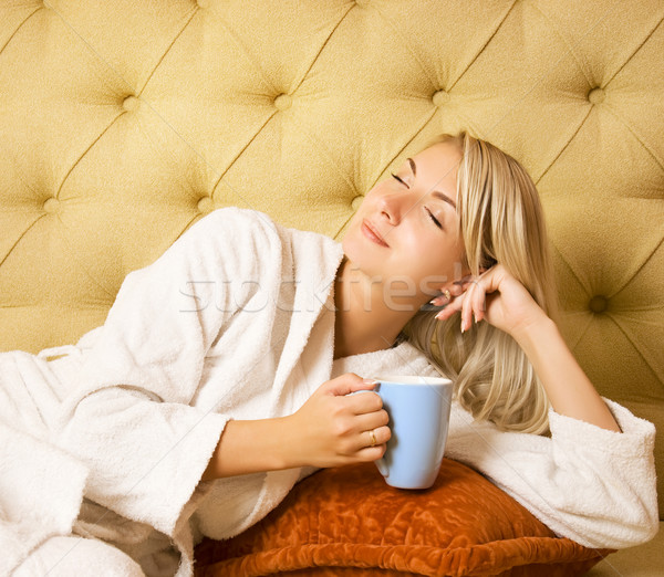 Bautiful young woman sitting on a bed and drinking cofee in the  Stock photo © Nejron