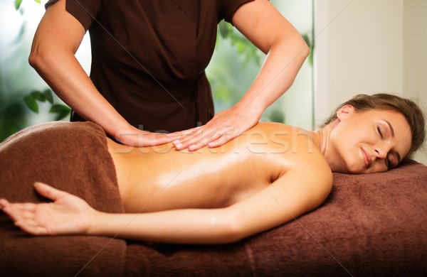Beautiful young woman having massage in a spa salon Stock photo © Nejron