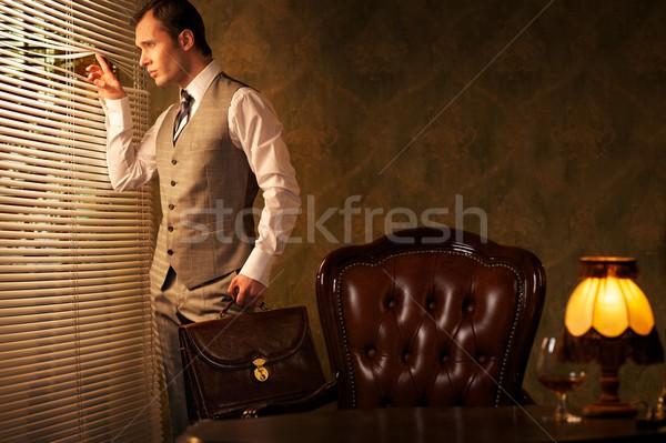 Retro man with a briefcase looking through jalousie.  Stock photo © Nejron