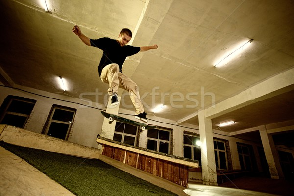 Young man performing a stunt in a skatepark Stock photo © Nejron