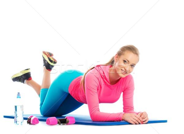 Beautiful girl doing fitness exercise on a floor mat  Stock photo © Nejron