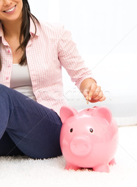 Cheerful young woman sitting on a carpet with piggybank Stock photo © Nejron
