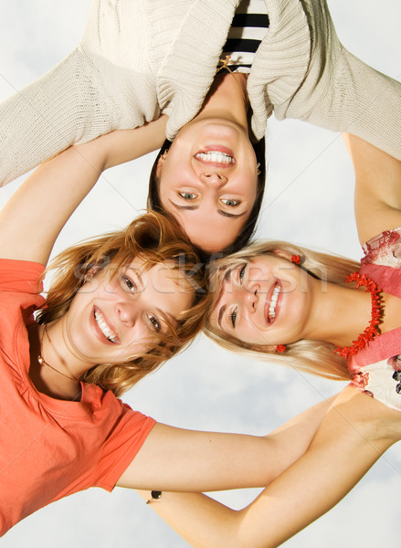 Group of happy friends standing in circle Stock photo © Nejron