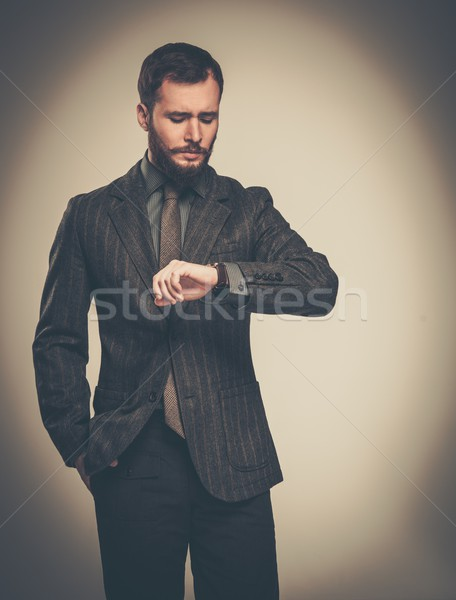 Handsome well-dressed man with beard looking at his wrist watch Stock photo © Nejron