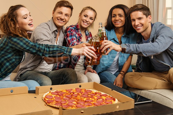 Group of young multi-ethnic friends with pizza and bottles of drink celebrating in home interior Stock photo © Nejron