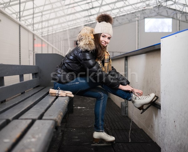 Stock photo: Cheerful girl putting on skates  on ice skating rink