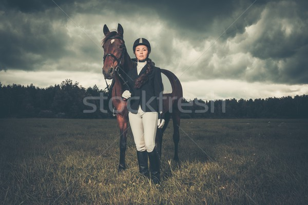 Beautiful girl standing near horse outdoors against moody sky Stock photo © Nejron