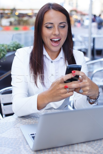Surprised young brunette woman alone with laptop and mobile phone in summer cafe Stock photo © Nejron