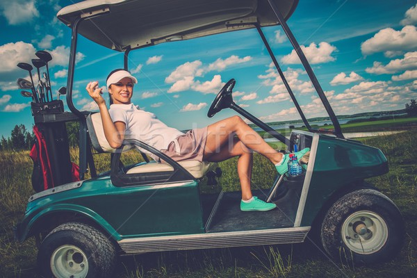 Young cheerful woman driving golf cart  Stock photo © Nejron