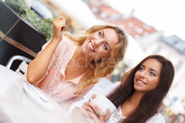 Two beautiful girls with cups chatting in summer cafe  Stock photo © Nejron