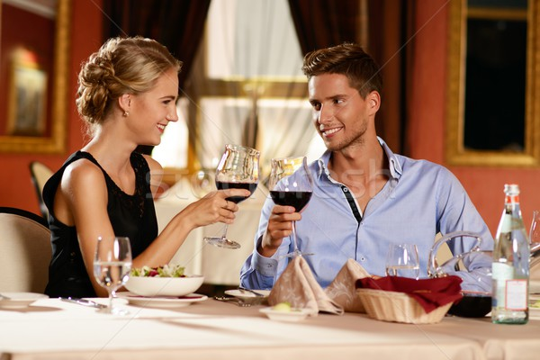 Beautiful young couple with glasses of wine in restaurant Stock photo © Nejron