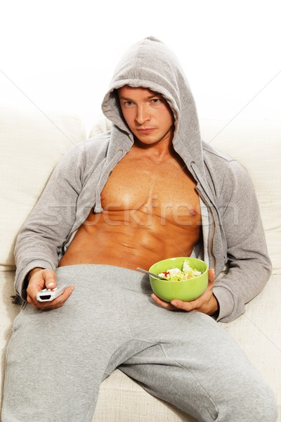 Sporty man in grey hoodie with muscular torso eating fresh salad Stock photo © Nejron