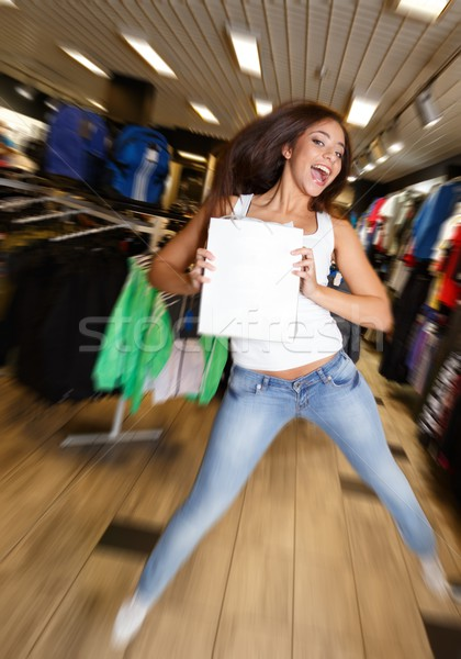 Beautiful happy brunette girl with shopping bag jumping in a sport outlet Stock photo © Nejron
