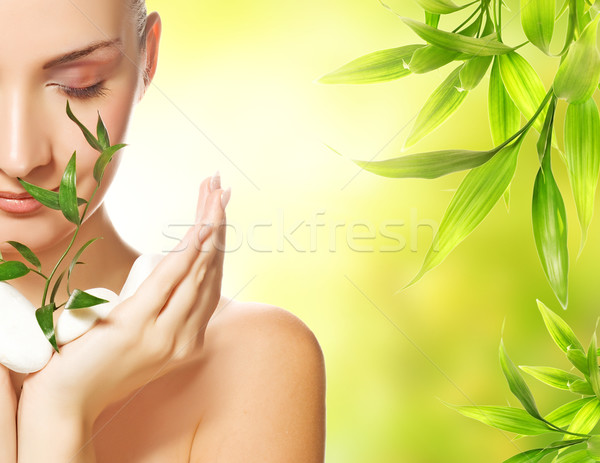 Stock photo: Beautiful young woman holding plant growing up through stones