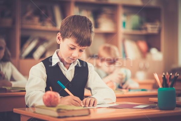 Miraculous Little Schoolboy Sitting Behind School Desk During Lesson In Beutiful Home Inspiration Ommitmahrainfo