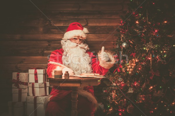 Santa Claus in wooden home interior sitting behind table and writing letters with quill pen Stock photo © Nejron