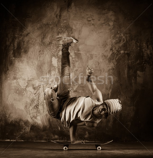 Toned picture of young man  doing acrobatic movements on skateboard Stock photo © Nejron