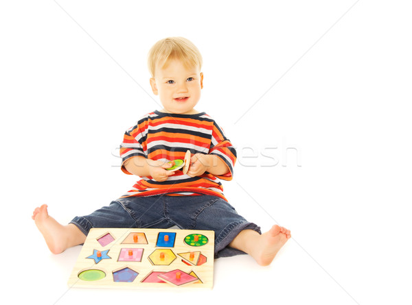 Stock photo: Beautiful young child playing intellectual game. Isolated on whi