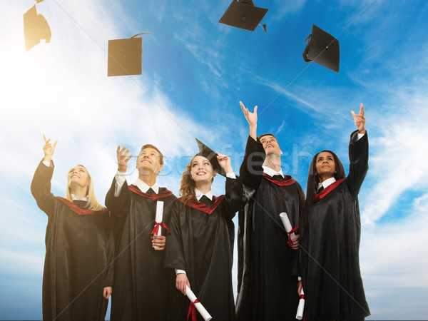 Happy multi ethnic group of graduated young students throwing hats in the air Stock photo © Nejron