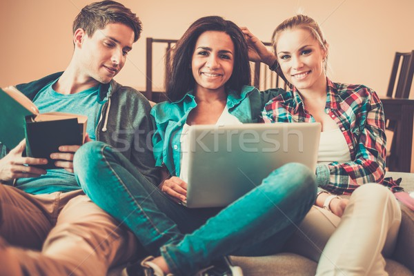 Three young students preparing for exams in home interior  Stock photo © Nejron