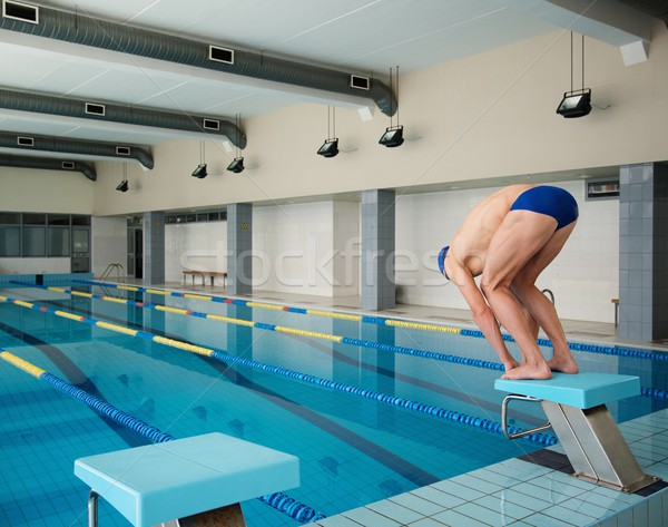 Young muscular swimmer in low position on starting block in a swimming pool Stock photo © Nejron