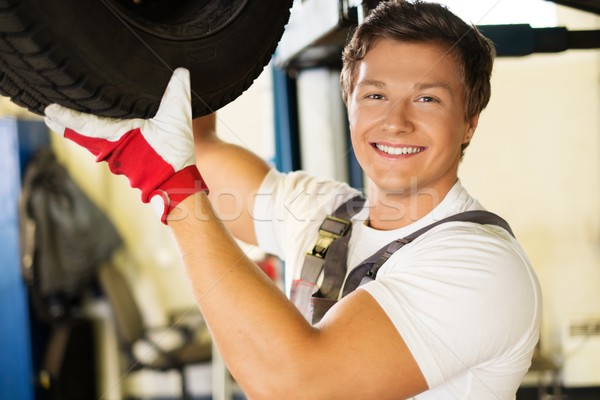 Cheerful serviceman checking suspension in a car workshop  Stock photo © Nejron