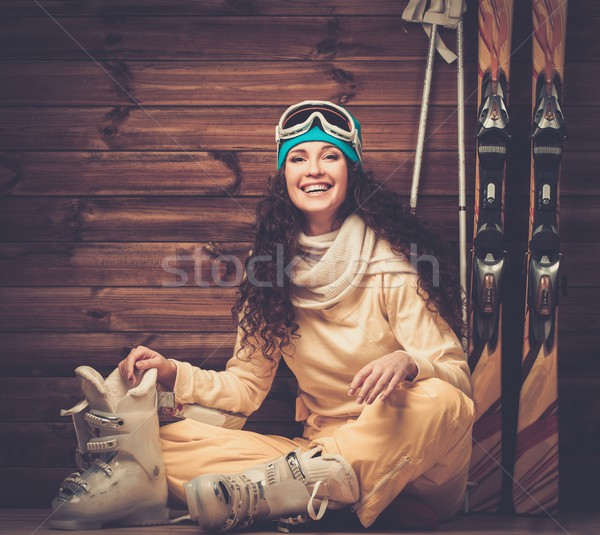 Happy woman with skis and ski boots sitting on a floor near wooden wall Stock photo © Nejron