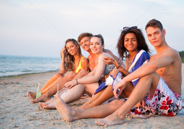 Group of multi ethnic friends with drinks relaxing on a beach Stock photo © Nejron