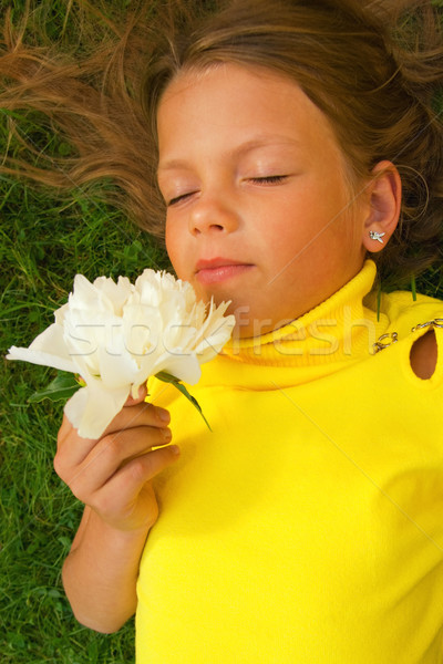 Little girl with a white flower lying on a green grass Stock photo © Nejron