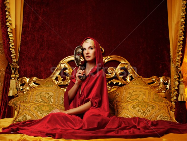 Beautiful woman with a carnival mask sitting in bed Stock photo © Nejron