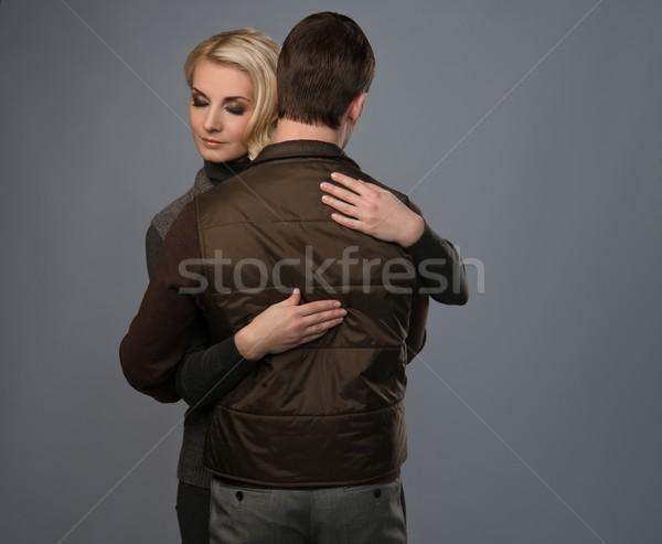 Embracing young couple isolated on grey Stock photo © Nejron