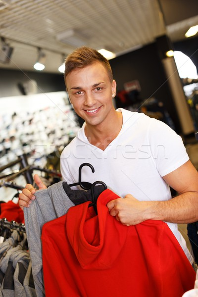 Handsome young man choosing sports wear in a sport outlet Stock photo © Nejron
