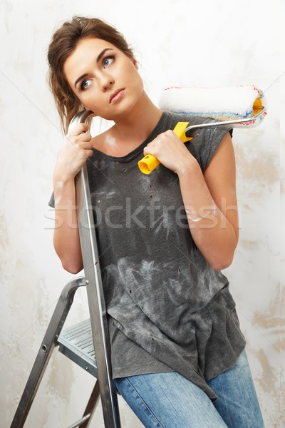 Pensive young woman sitting on a ladder with painting roller  Stock photo © Nejron
