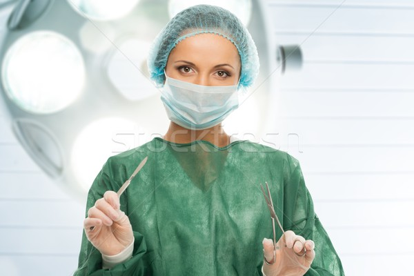 Young woman doctor with scalpel and scissors in surgery room interior  Stock photo © Nejron