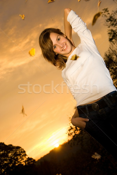 Beautiful young girl at sunset time and falling autumn leaves ar Stock photo © Nejron
