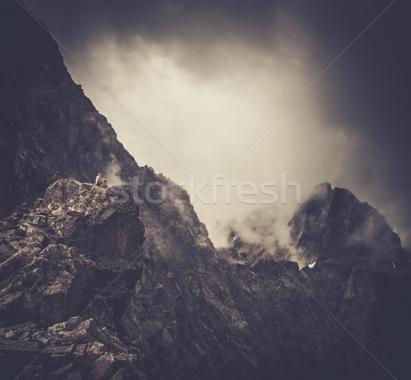Woman hiker sitting on a mountain peak  Stock photo © Nejron