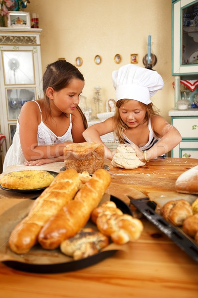 Stock photo: Two little girls trying to cook homemade pastry