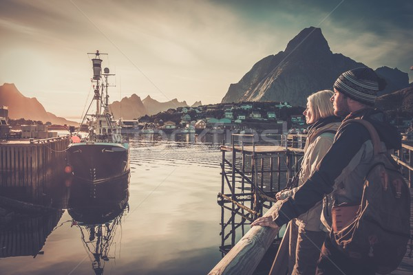 Young travellers couple looking at sunset in Reine village, Norway Stock photo © Nejron
