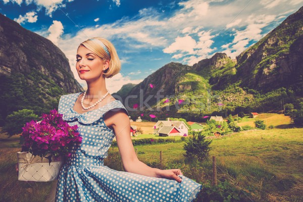 Lovely woman in  blue dress with  basket of flowers against small village view Stock photo © Nejron