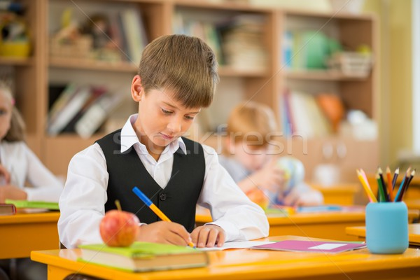 Stock photo: Little schoolboy  sitting behind school desk during lesson in school