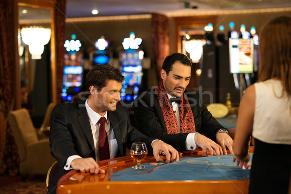 Two young cheerful men behind table in a casino Stock photo © Nejron