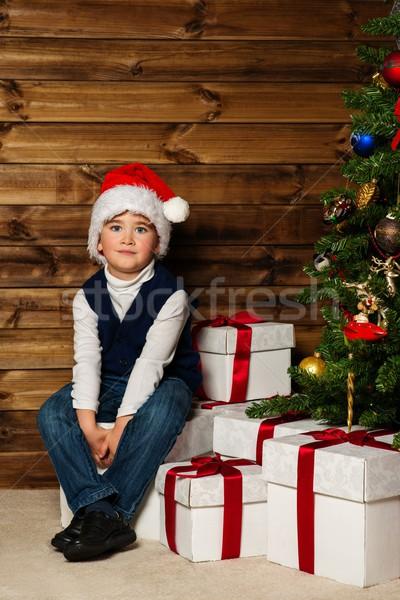Kicsi fiú mikulás kalap ajándék doboz karácsonyfa Stock fotó © Nejron