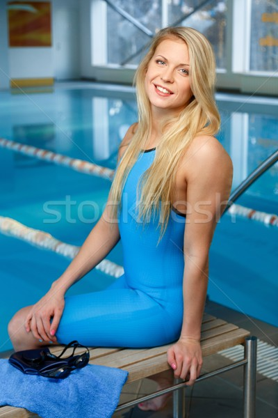 Young blond woman in swimming suit sitting on a bench near pool Stock photo © Nejron