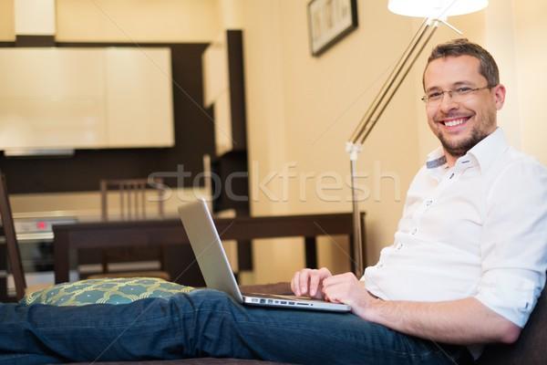Młody człowiek siwe włosy laptop sofa domu wnętrza Zdjęcia stock © Nejron