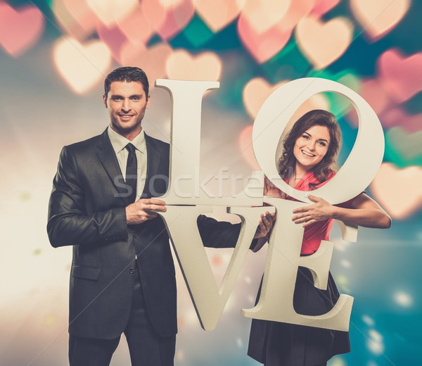 Couple holding word LOVE over blurred background Stock photo © Nejron