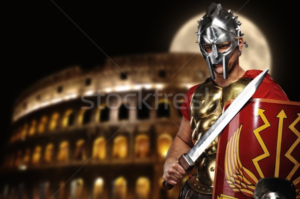 Stock photo: Roman legionary soldier in front of coliseum at night time