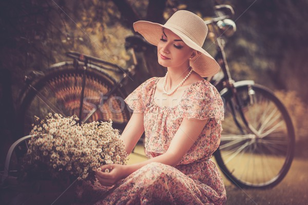 Beautiful retro woman with basket of flowers n and bicycle behind her Stock photo © Nejron