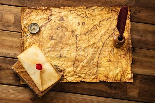 Quill pen, compass and envelope on old map over wooden background  Stock photo © Nejron
